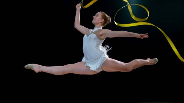 SLO MO SPEED RAMP LD Rhythmic gymnast swirling her golden ribbon and doing a split leap