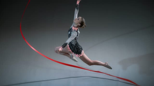 SLO MO Rhythmic gymnast swirling her red ribbon in a large circle while performing a stag leap