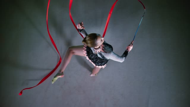 SLO MO LD Rhythmic gymnast swirling her red ribbon while performing the attitude pivot Slow motion wide right above locked down shot of a rhythmic gymnast performing the attitude pivot and swirling a red ribbon. Shot in Slovenia. performer stock videos & royalty-free footage