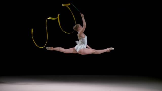 SLO MO SPEED RAMP LD Rhythmic gymnast swirling her ribbon during a split leap performance