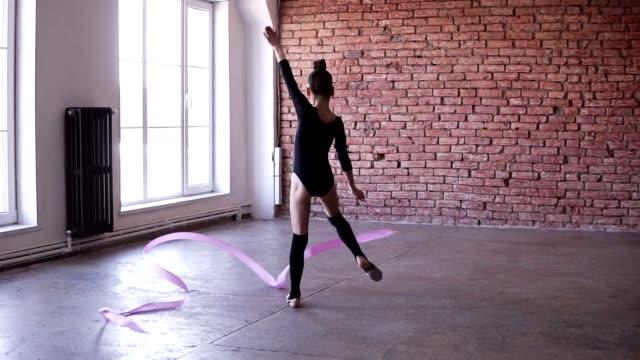 女の子のための新体操。一人で踊る stuido で運動かわいい女の子。ダンス, ピンクのリボンでスピニング.スローモーション映像。背景にレンガの壁 - ダンススタジオ点の映像素材/bロール