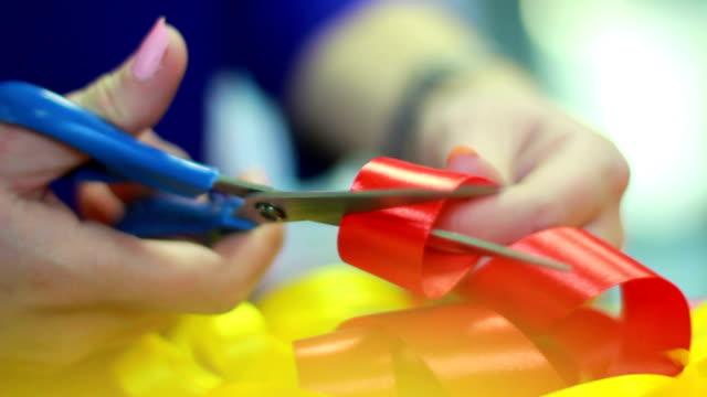 şeritler dekorasyon. kırmızı kurdele kesme eller. saten ambalaj bandı - ribbon stok videoları ve detay görüntü çekimi