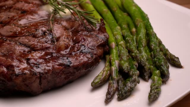 vídeos de stock e filmes b-roll de ribeye beef steak on a plate with asparagus ready to eat - meat texture