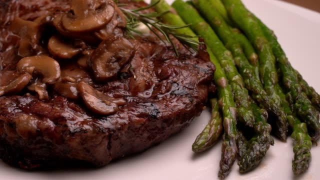 Ribeye Beef steak on a plate with asparagus ready to eat