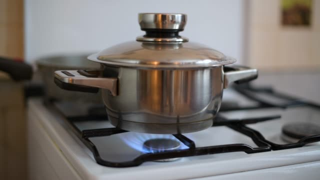 rice is cooked on a gas stove and water escapes from under a closed lid.