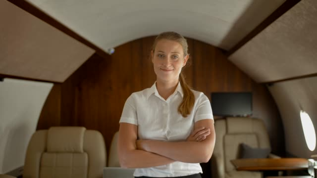 Rich businesswoman inside of luxury private business jet smiling