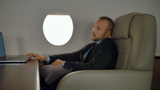 Rich entrepreneur working on notebook inside of luxury jet