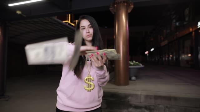 vidéos et rushes de fille riche jetant l'argent à la ville de nuit - lancer