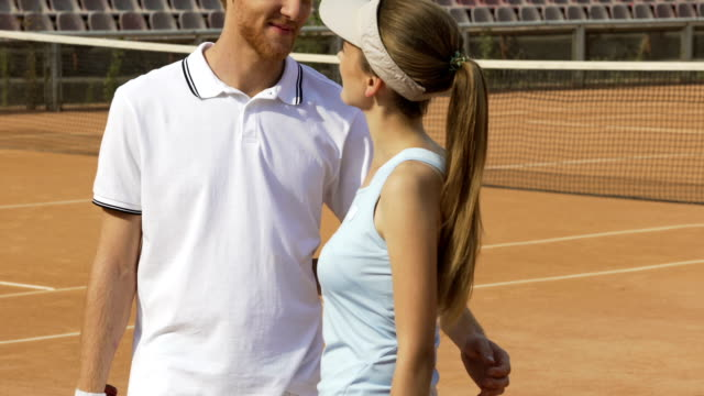 Rich loving couple talking about future tennis match on court, hobby and sport Rich loving couple talking about future tennis match on court, hobby and sport charming stock videos & royalty-free footage