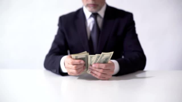 reicher mann zählen bündel dollar-banknoten, geschäftsmann, die schätzung der einnahmen - billionär stock-videos und b-roll-filmmaterial