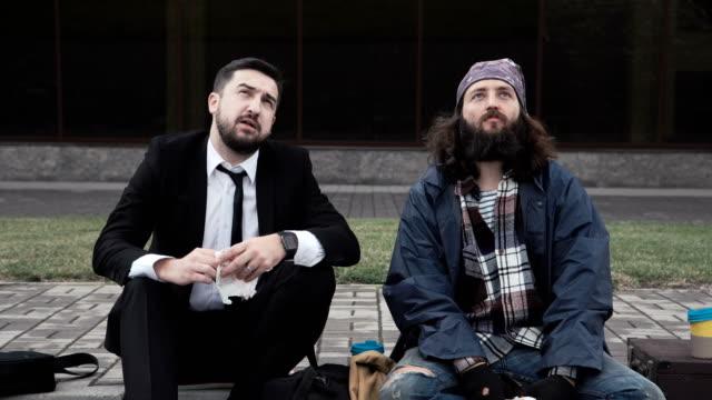 vídeos de stock, filmes e b-roll de homem rico comer ao lado de um mendigo enquanto espera - contrastes