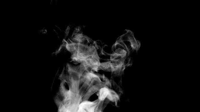 Rich Steam from a Cup of Tea White steam rises light, graceful twists on a black background. The jet lifted out of the cup of hot water. Shooting at a rate of 120fps. Footage is perfect for the top layer with different blending modes steam stock videos & royalty-free footage