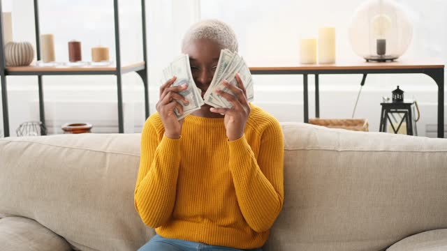 Rich woman waving fan of banknotes