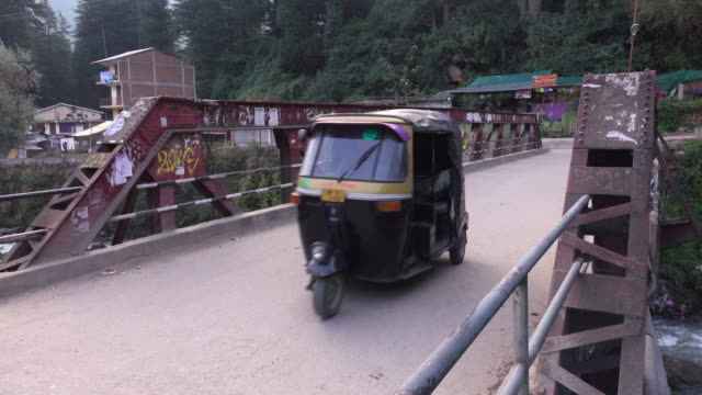 Rickshaws riding across the bridge to Old Manali, Himachal Pradesh, India video