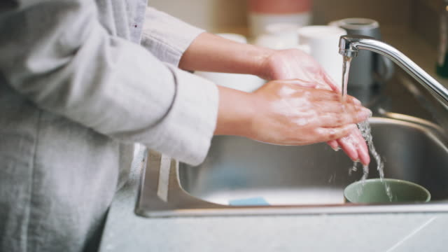 Ridding myself and my kitchen of germs 4k video footage of an unrecognizable woman washing her hands in the kitchen sink at home kitchen sink stock videos & royalty-free footage