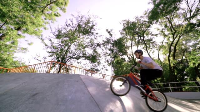 bmx ryttare gör tricks i extrema park under solnedgång, slowmotion - skatepark bildbanksvideor och videomaterial från bakom kulisserna