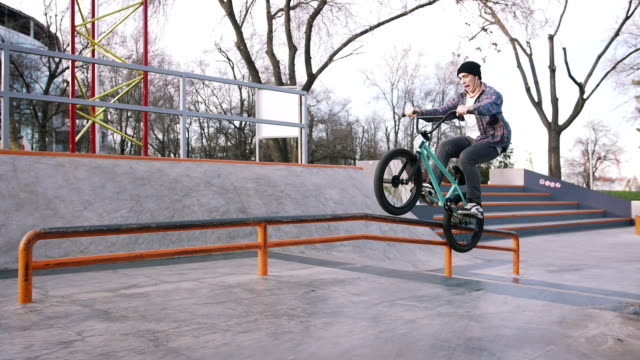 BMX rider doing tricks in street plaza, bicycle stunt rider in cocncrete skatepark, super slow motion