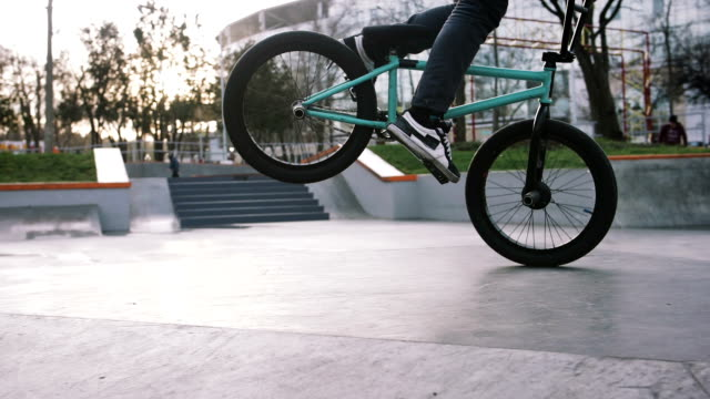 BMX rider doing tricks in street plaza, bicycle stunt rider in cocncrete skatepark, super slow motion, close up