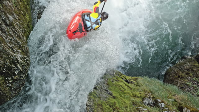 SLO MO Rider in a yellow whitewater kayak dropping a waterfall