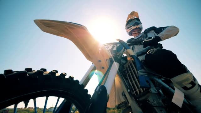 fmx rider is sitting on his motorbike against the sun - supercross video stock e b–roll