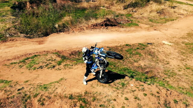 a rider is standing and vertically holding his motorcycle - supercross video stock e b–roll