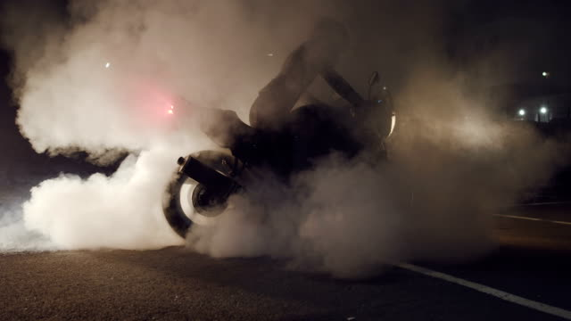 rider on streetbike burning rubber. - bike tire tracks video stock e b–roll