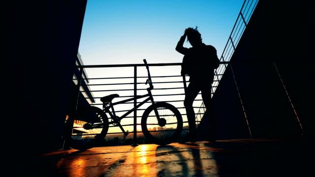 Rider rests on a sunset background. Active Teenager silhouette.