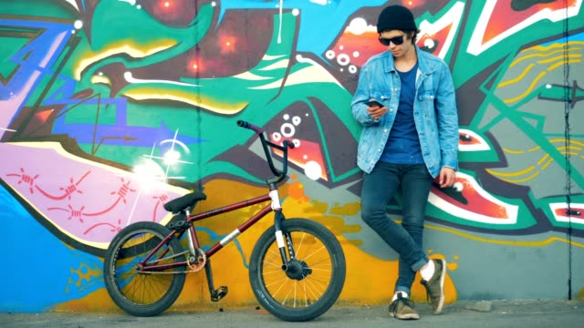 ライダーは手に電話で立っています。若いスタイリッシュな白人男性ティーンエイジャー。 - street graffiti点の映像素材/bロール