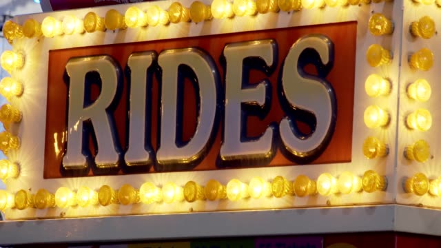 Rides sign at night at carnival fair grounds.