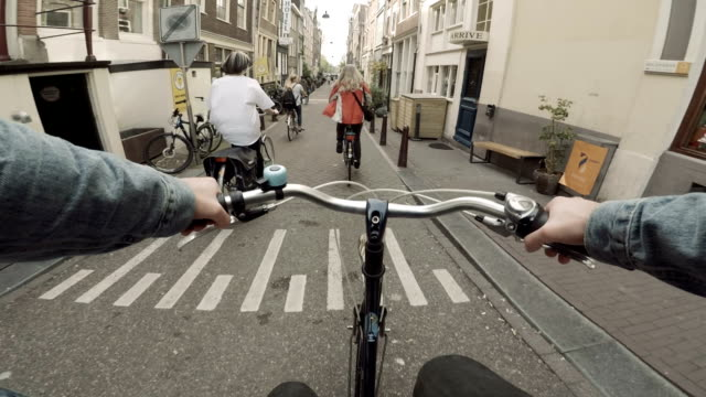 riding a bike down the streets of amsterdam, netherlands - amsterdam video stock e b–roll