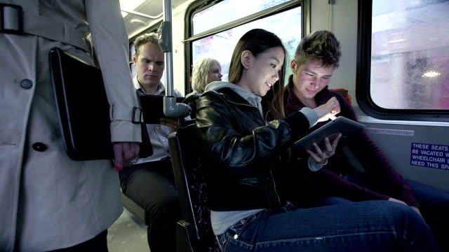 riding a bus and using digital tablet for internet video