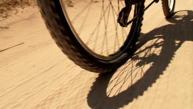 montare su una mountain bike su sabbia su strada - bike tire tracks video stock e b–roll