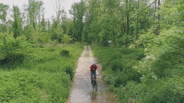 aerial riding a mountain bike through a puddle - percorso per bicicletta video stock e b–roll
