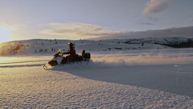 slo mo riding a snowmobile at sunset - fiordi video stock e b–roll