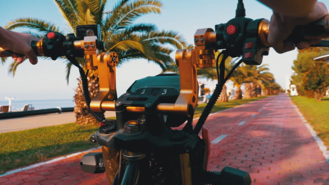 POV Riding an Electric Bike on a Red Bike Path with Palm Trees in the Resort Town