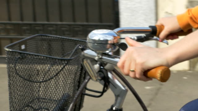 Riding and Ringing Bicyle Bell Female ringing the bicycle bell ounted in the handlebar for announcing her presence in traffic. handlebar stock videos & royalty-free footage