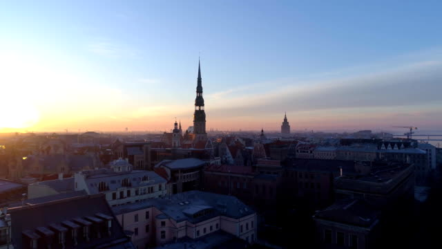riga city church sunrise buildings old down town drone - латвия стоковые видео и кадры b-roll