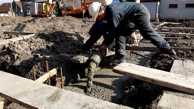 Riggers, workers are holding pump hose to pouring fresh concrete into building foundation Construction workers are pouring concrete in building foundation, directing the pump tube on right direction. civil engineering stock videos & royalty-free footage