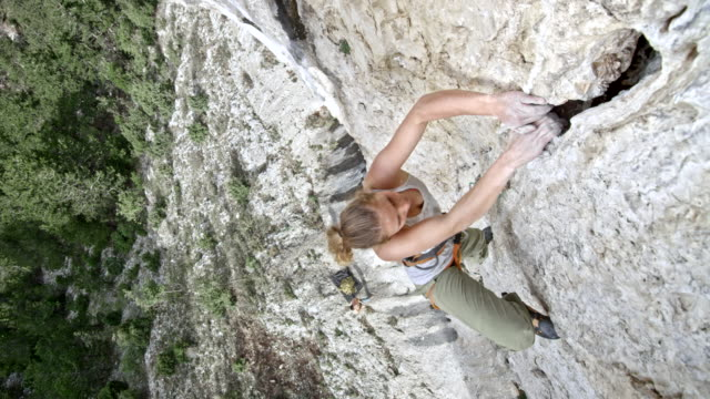 Right above a female rock climber ascending a cliff