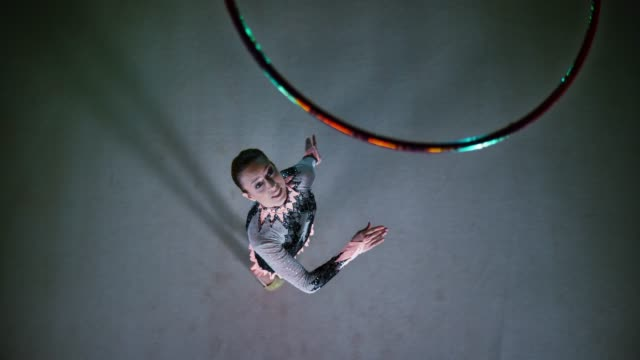 vídeos de stock, filmes e b-roll de slo mo rampa de velocidade ld logo acima de uma ginasta rítmica jogando seu aro no ar e girando antes de pegá-lo - artista