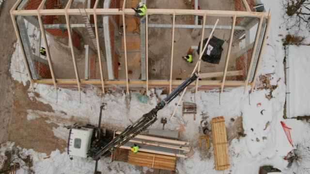 AERIAL Right above the crane lifting a supportive beam to the rooftop