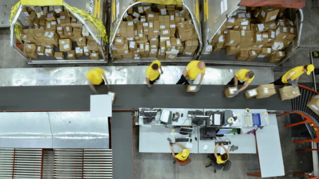 TIME-LAPSE Right above the warehouse workers taking packages off the conveyor belt Time-lapse right above shot of workers in the warehouse taking packages off the conveyor belt for further distribution. Shot in Slovenia. warehouse stock videos & royalty-free footage