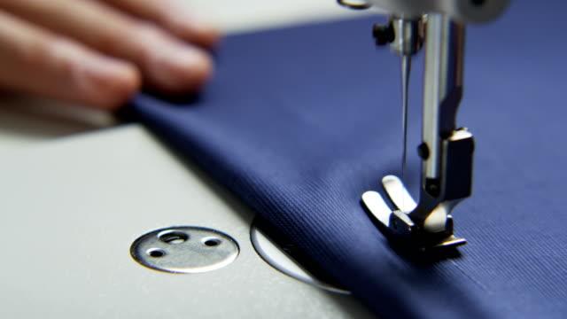 vidéos et rushes de main droite d'un tailleur à l'aide d'une machine à coudre - coudre