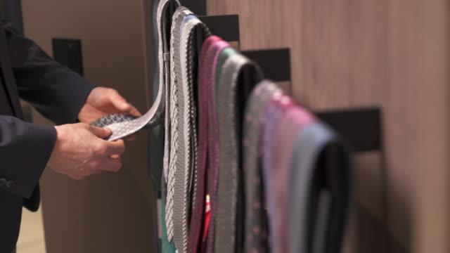 vídeos y material grabado en eventos de stock de tiro de derecha a izquierda de un cliente eligiendo lazos en moda masculina ropa boutique. selección de ropa elegante para hombres. - corbata
