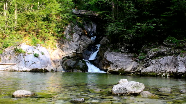 Rindbach waterfall with wooden bridge, forest and small lake. Austria alps mountain