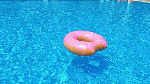 vídeos de stock e filmes b-roll de ring float in blue swimming pool - brinquedos na piscina