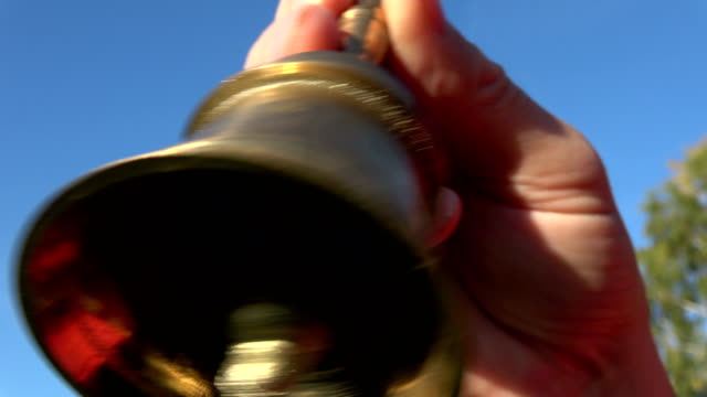 ringing brass bell on sky background and beautiful sound video