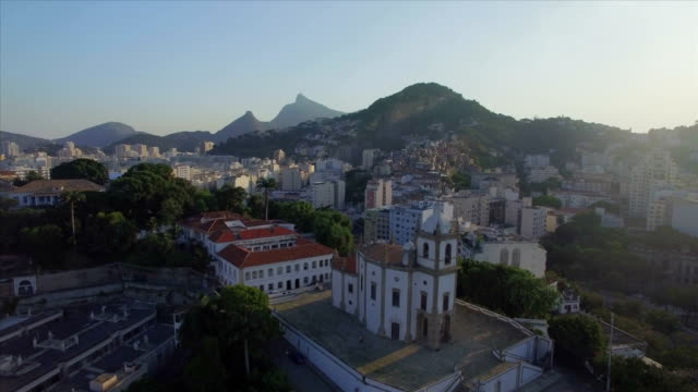 Rio de Janeiro Aerials: wide move towards Nossa Senhora da Gloria Church in the foreground and Christ the Redeemer in the background video
