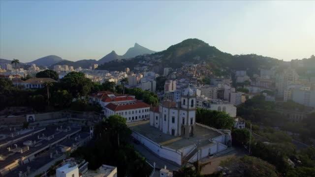 Rio de Janeiro Aerials: wide move upwards with Nossa Senhora da Gloria Church in the foreground and Christ the Redeemer in the background video