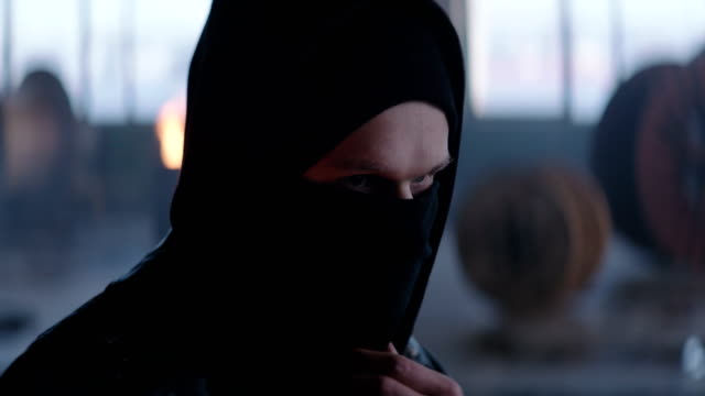 Riot man puts black balaclava in industrial background 4k, slow motion ninja stock videos & royalty-free footage